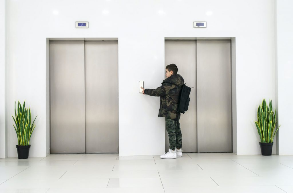 Boy with casual clothes and white sneakers call the elevator. White contemporary building interior.